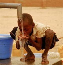 Boy with yellow shirt drinking water